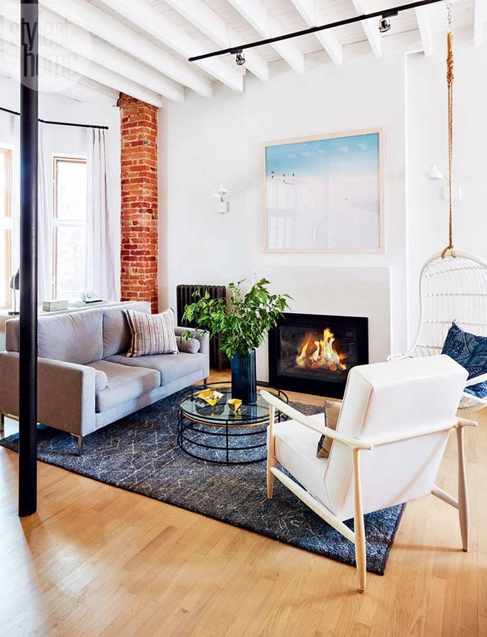 Уютный интерьер гостиной с камином и подвесным креслом фото