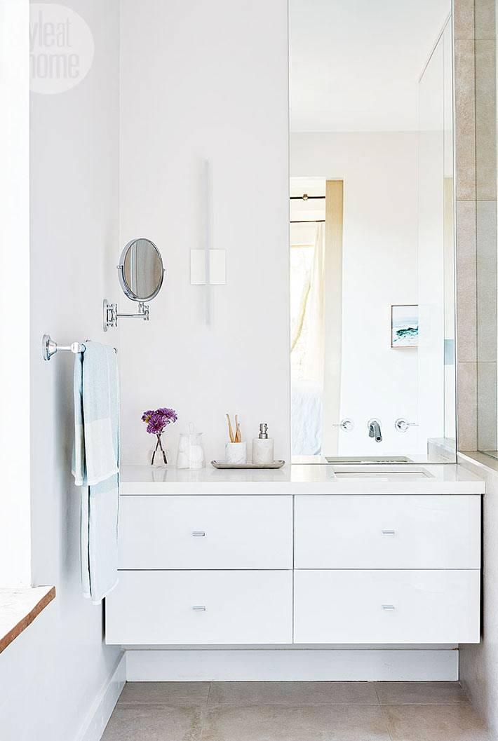 большая белая тумба под раковиной в ванной комнате