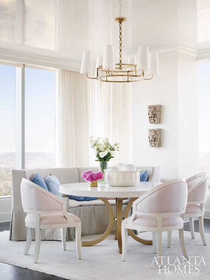 кргулый стол и мягкие стулья зефирного цвета в интерьере