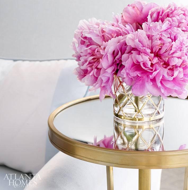 круглый золотой столик с пионами в стеклянной вазе