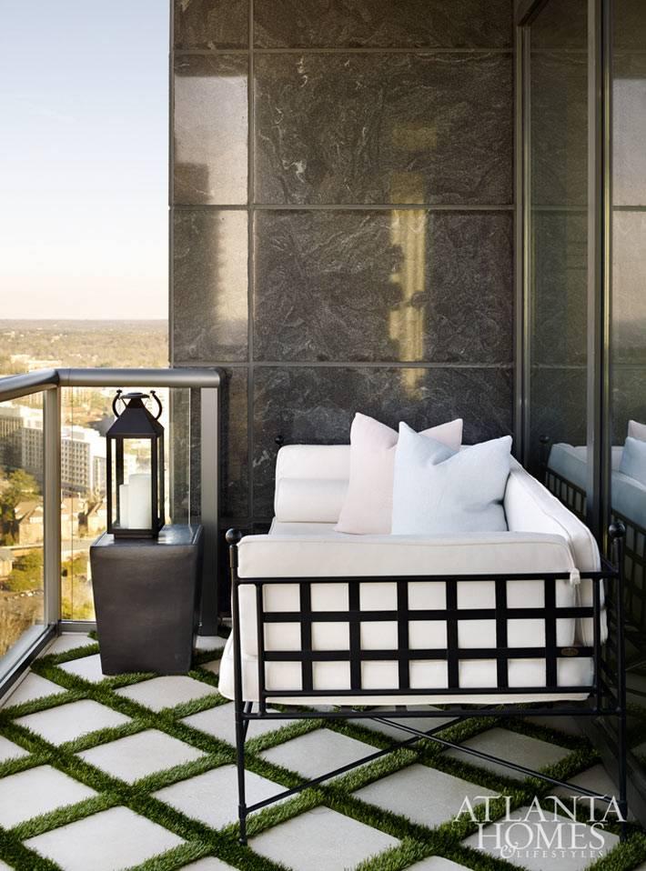 Уютный белый диванчик на открытом балконе в небоскребе фото