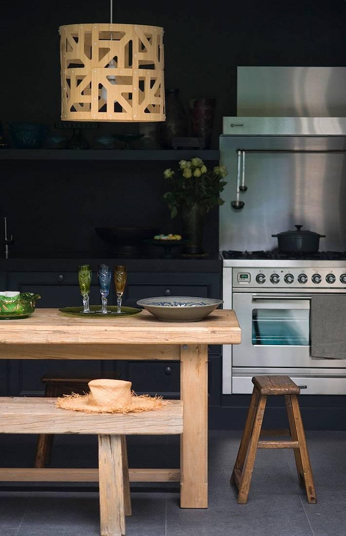 Кухня черного цвета со столом и люстрой из светлого дерева фото