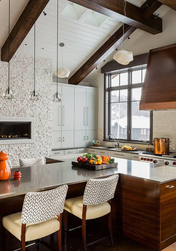 Большая красивая кухня в доме со встроенным камином фото