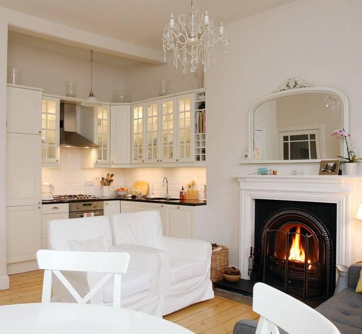Красивая белая кухня с очагом в камине фото