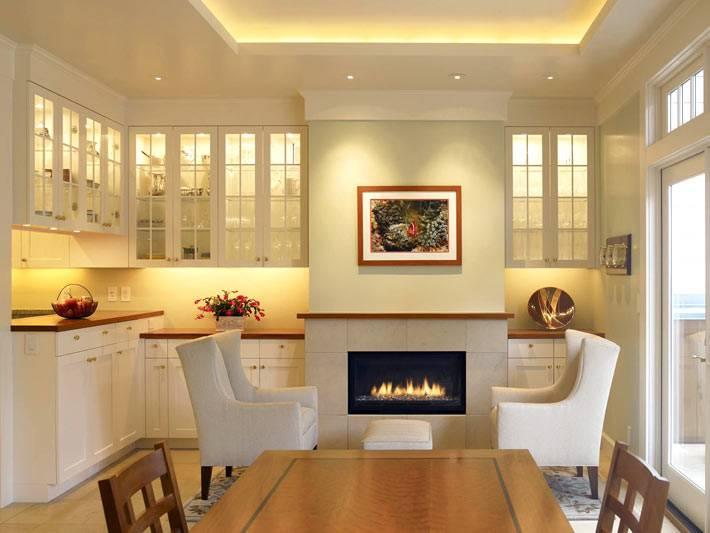 Большая кухня с креслами возле камина фото