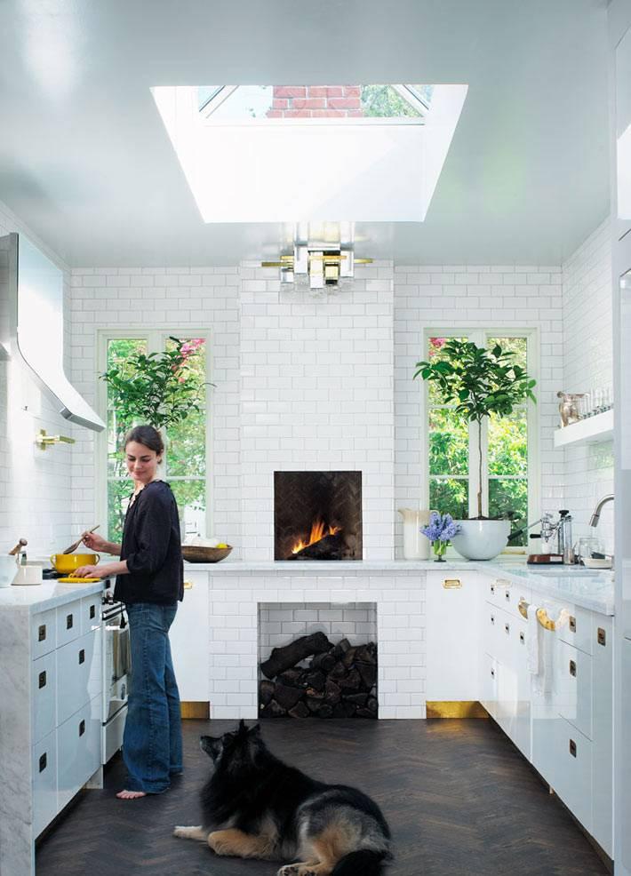 Белый интерьер кухни с камином и мансардным оном фото