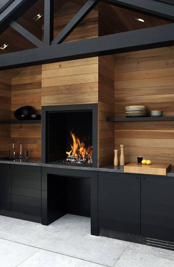 кухня черного цвета с настоящим камином фото