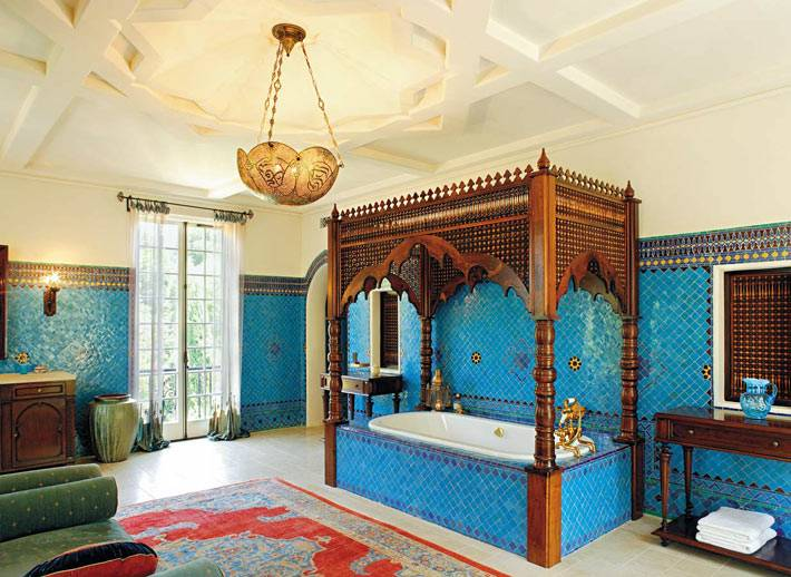 большой интерьер ванной с синей плиткой на стенах