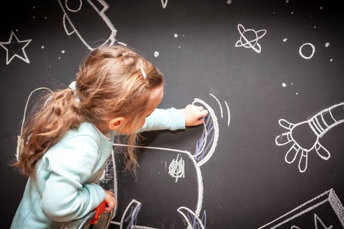 ребенок рисует мелом на черной стене в кухне фото