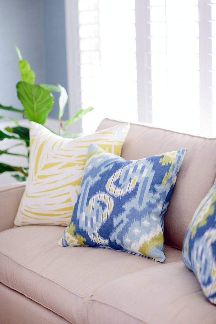яркие диванные подушки с узорами на бежевом диване