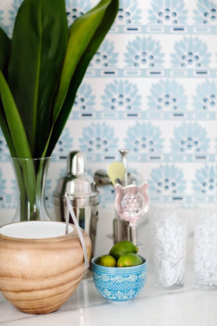 зеленые листья на фоне бледно-голубой стены кухни
