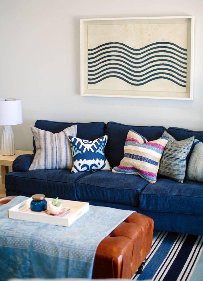 полосатые подушки на синем диване с гостиной комнате