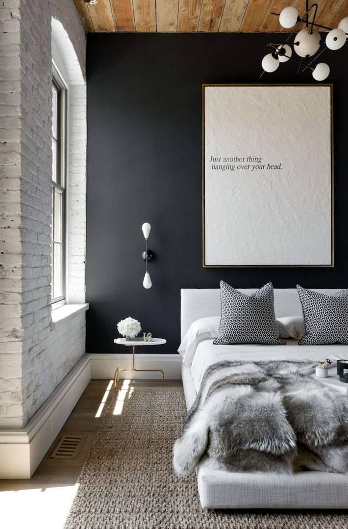 спальня с белой кирпичной стеной и деревянным потолком