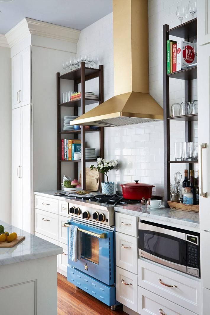 золотая вытяжка на белой кухне с синей духовкой