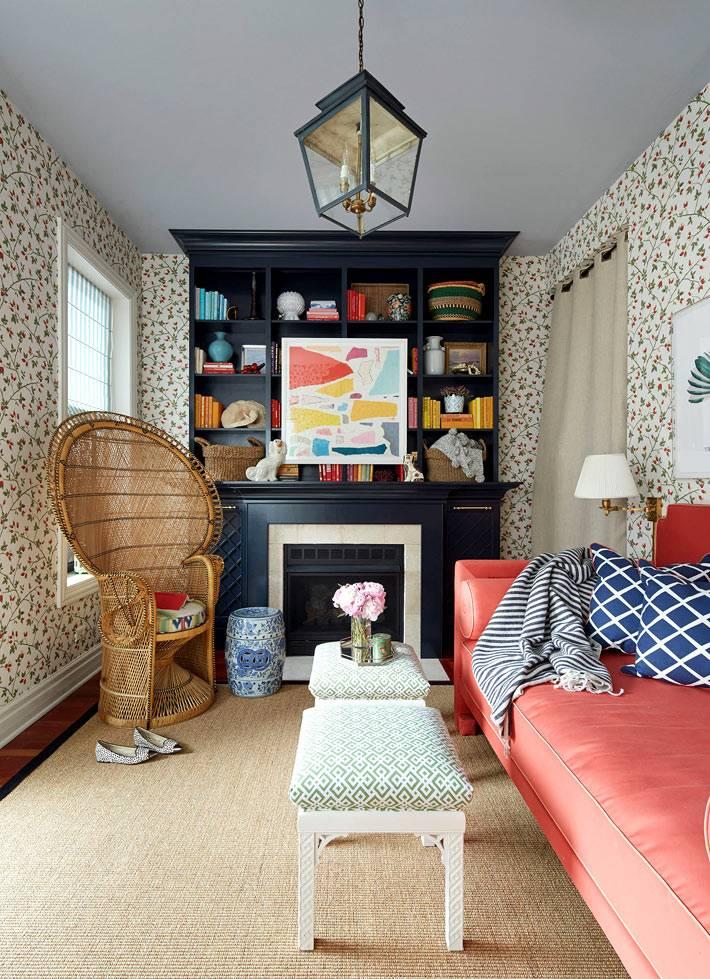 вытянутая комната с красными диваном и пестрыми обоями фото