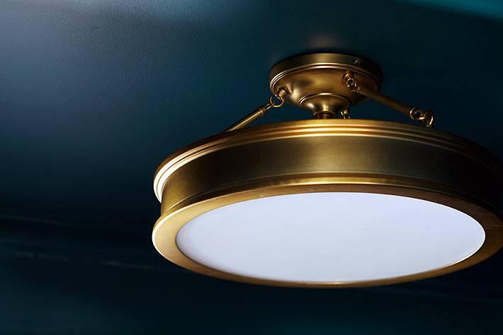 Латунная лампа гармонирует с синими стенами кухни фото