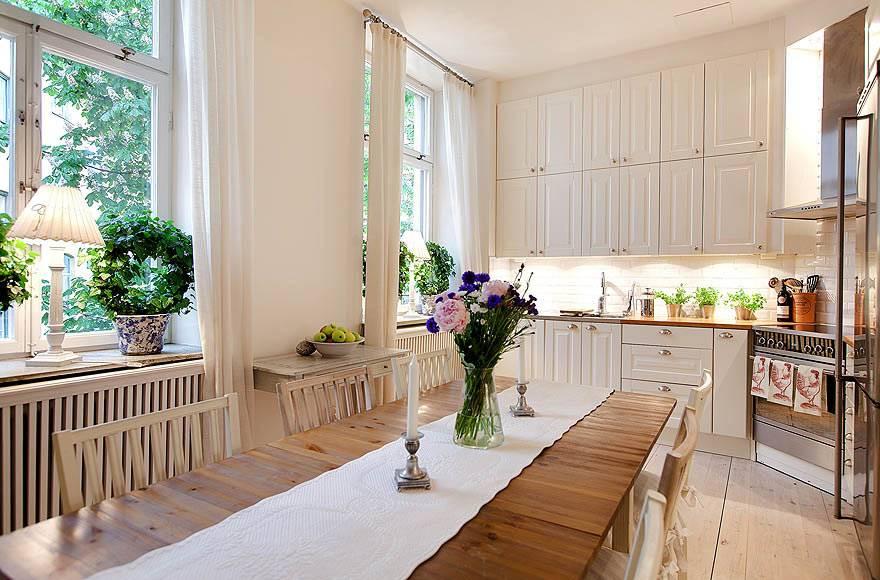 белая мебель на кухне и деревянный обеденный стол