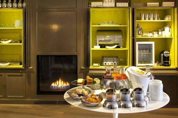 Яркие полки на темной кухонной мебели в отеле фото