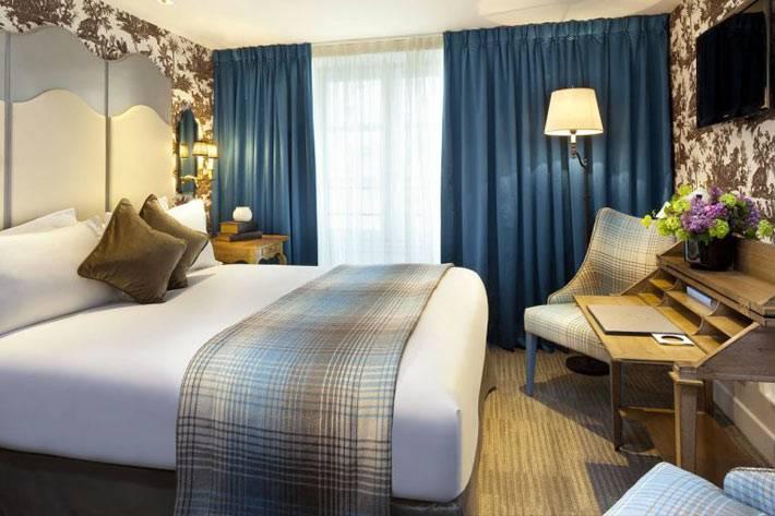 коричневые обои в цветочек и синие шторы в комнате