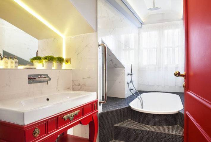 Красная тумба и ванная на подиуме в отельном номере фото