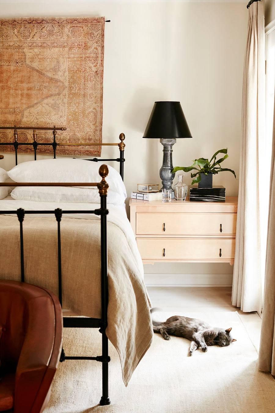Уютный интерьер спальни в бежевой гамме с ковром на стене