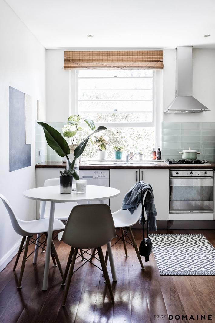 Небольшая кухонька с круглым обеденным столом фото