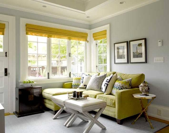 яркий желтый диван в комнате с серыми стенами фото
