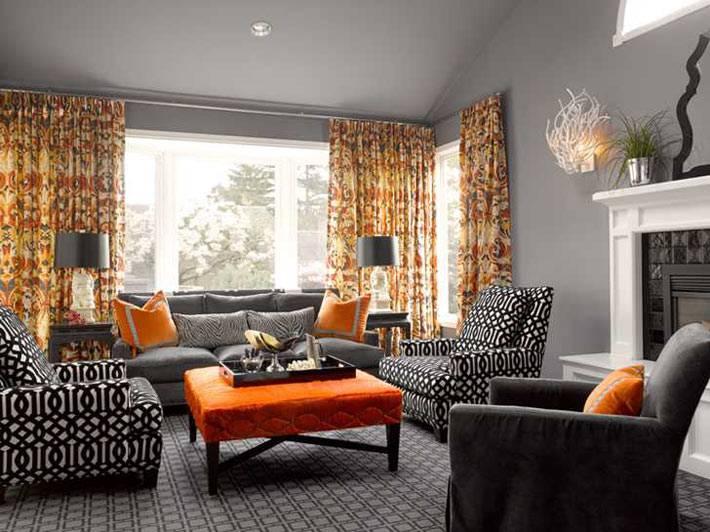 серая гостиная комната с оранжевыми акцентами на мебели