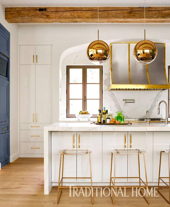 белая кухня с золотыми ручками, стульями и светильниками