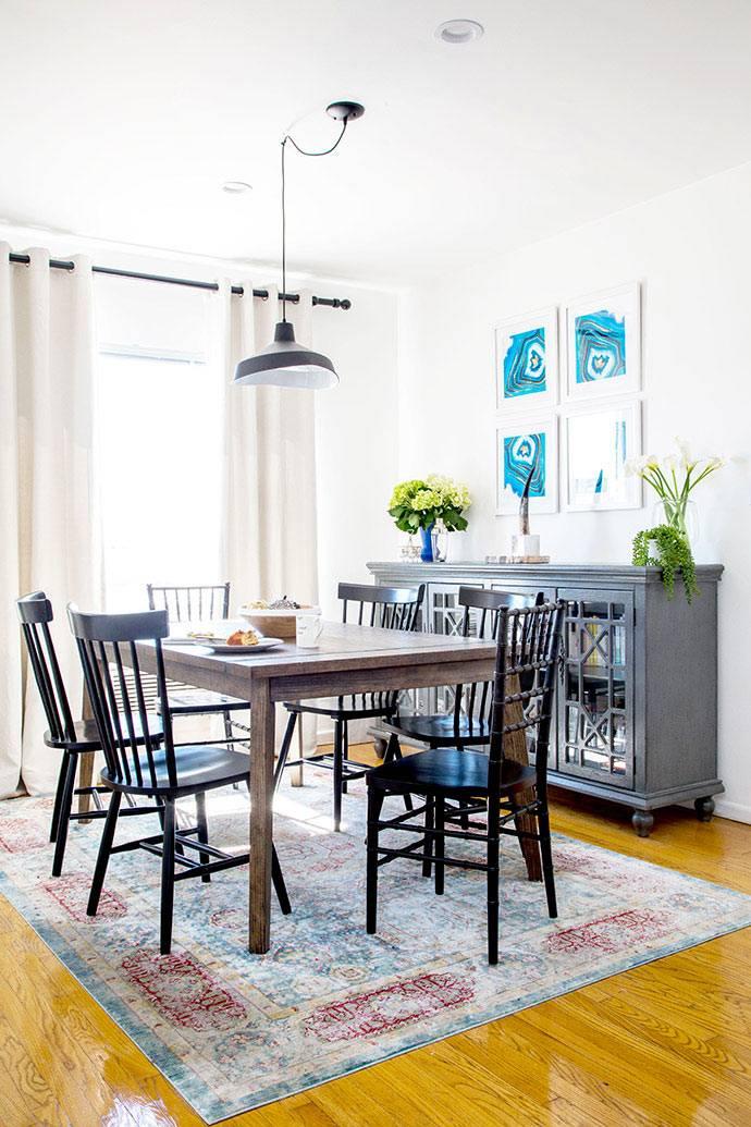 зона столовой с белыми стенами и подвесной люстрой фото
