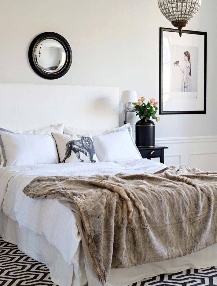 уютная спальня в светлых тонах и круглым зеркалом в черной раме