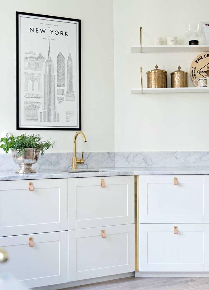 латунные смеситель и посуда на белой кухне фото
