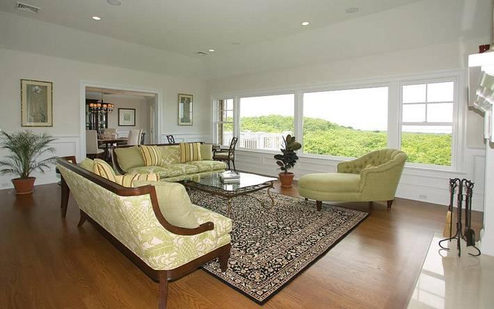 гостиная комната с большим окном и большим ковром