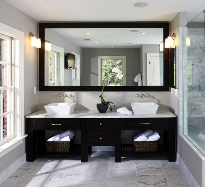 Большое зеркало и два умывальника в интерьере ванной комнаты фото