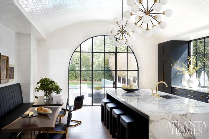 большая арочная кухня с мраморным столом и красивыми светильниками