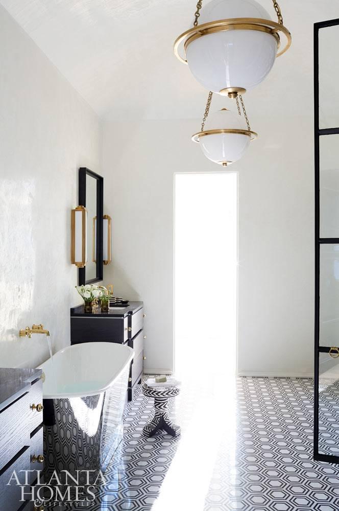 геометрический узор на полу ванной комнаты отражается на зеркальной поверхности ванны