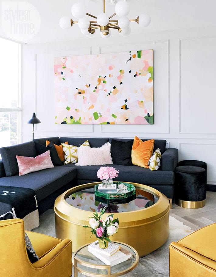 круглый журнальный стол золотистого цвета в центре гостиной фото