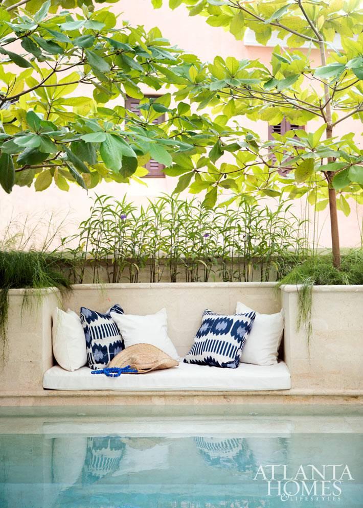 уютный уголок с матрасом и подушками возле бассейна