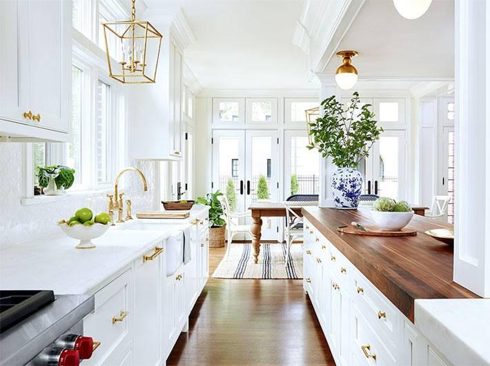 Большая белая кухня с деревянной столешницей фото