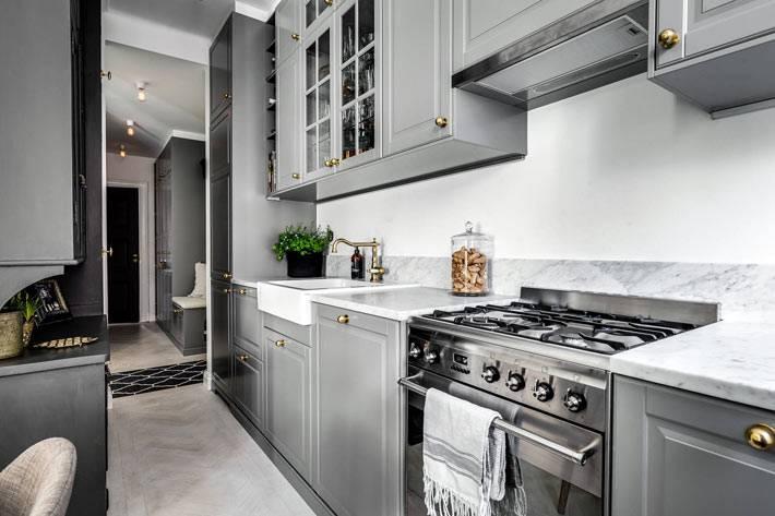 сочетание серого фасада кухонной мебели с латунными ручками