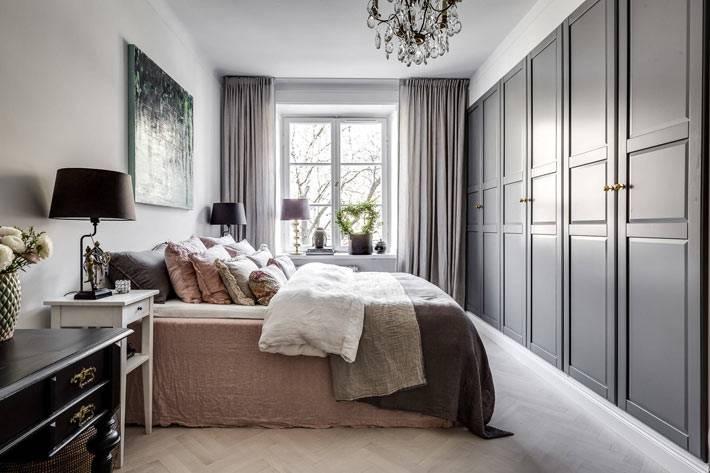 спальня с серыми шкафами и белыми прикроватными тумбами