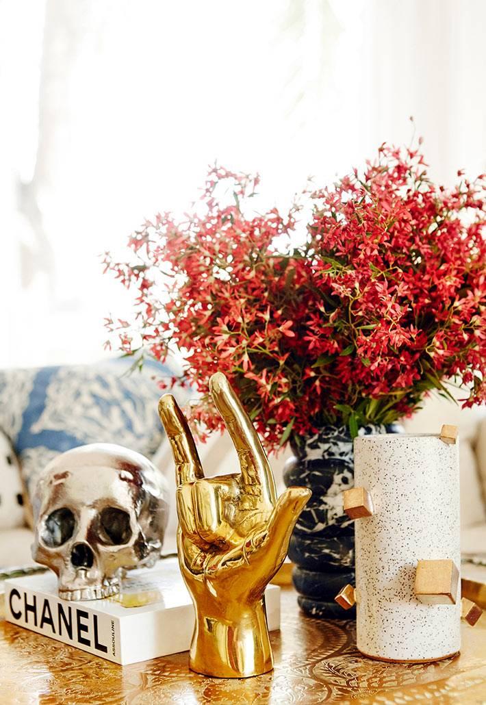 золотая рука и серебрянный череп как украшение на журнальном столе