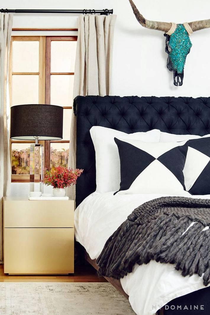 Композиция в спальне из черной кровати, золотистой тумбы и декоративной головой быка