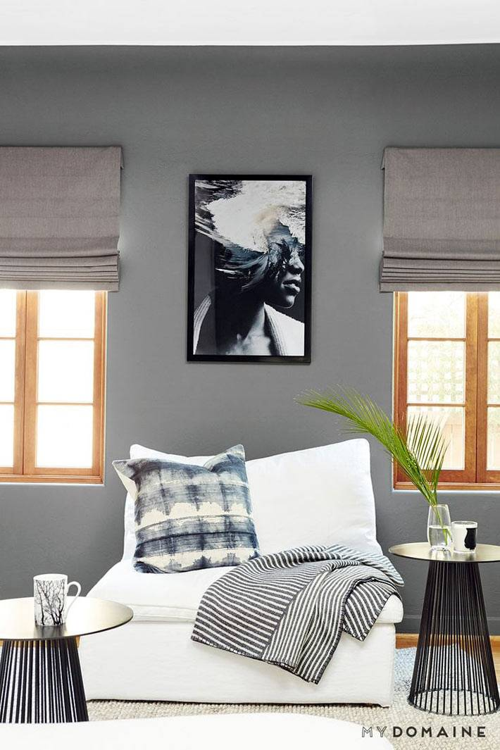 серый цвет стен в комнате с мягким белым креслом и кофейными столиками