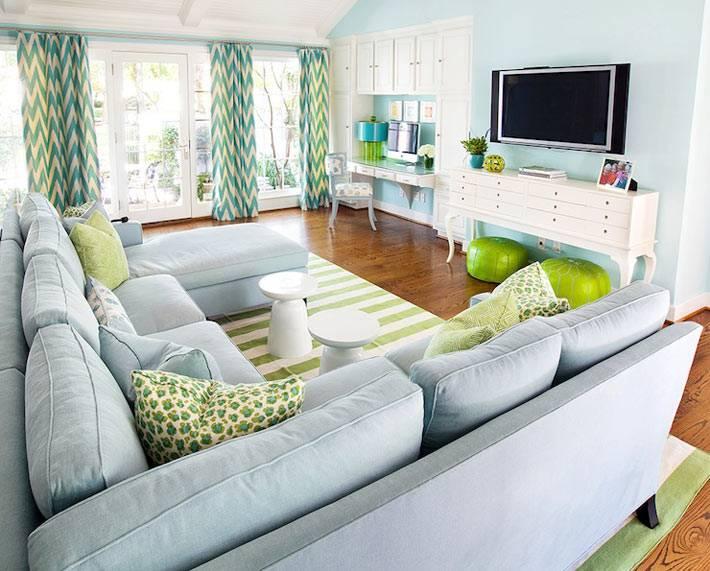голубая комната с диваном, телевизором и рабочим столом