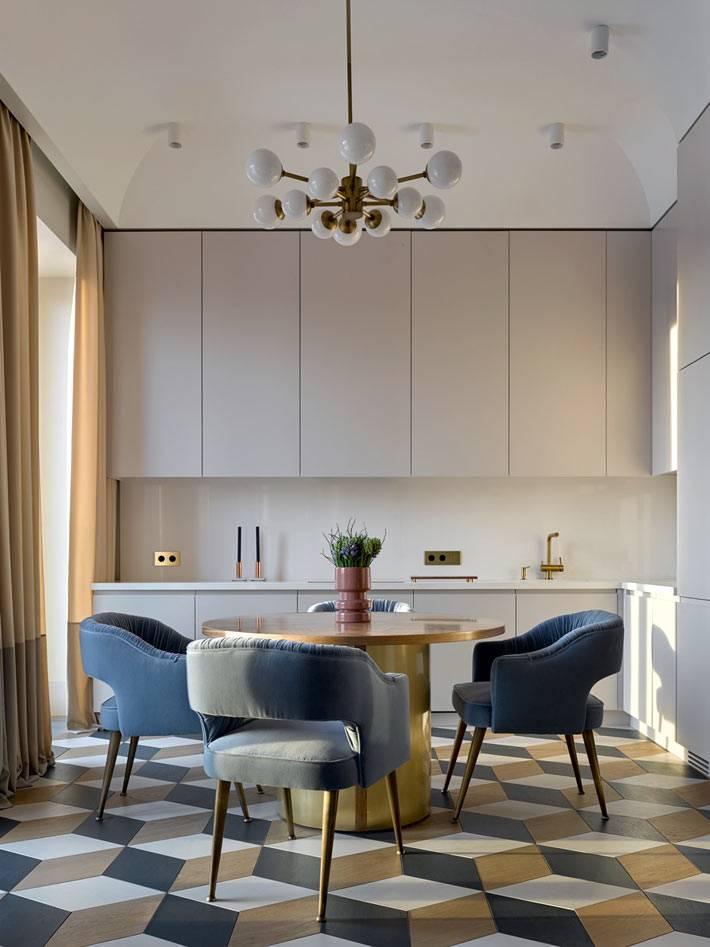 Круглый стол золотого цвета и удобные синие кресла в дизайне кухни