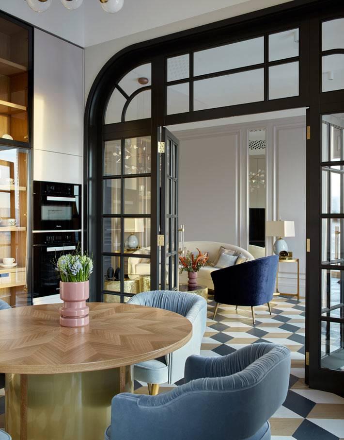 Дверь из стекла и черных перегородок между гостиной и кухней