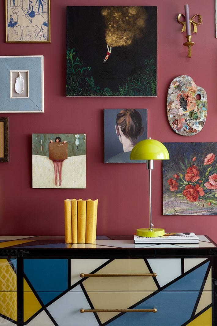 яркий комод и много картин на стене сливового цвета в квартире