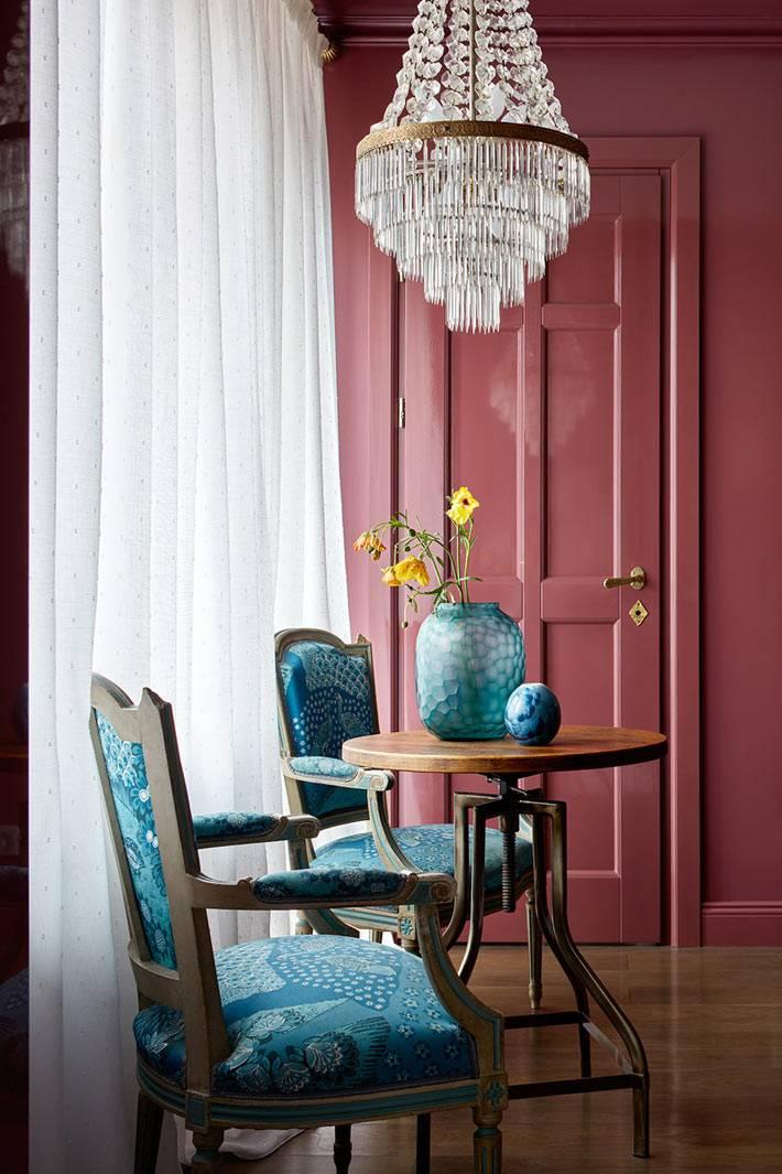 Хрустальная антикварная люстра над старинными синими стульями и круглым столом