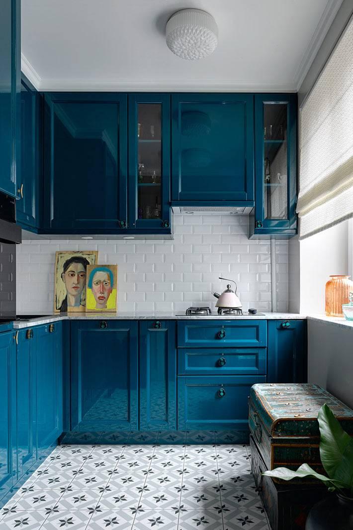 Темно синяя кухонная мебель и старинный сундук в интерьере кухни